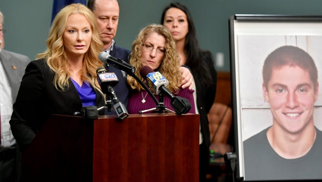 Jim and Evelyn Piazza stand by as Centre County District Attorney Stacy Parks Miller, left, announces the results of an investigation into the death of their son Timothy Piazza, seen in photo at right, a Penn State University fraternity pledge, during a press conference Friday, May 5, 2017, in Bellefonte, Pa. Timothy Piazza had toxic levels of alcohol in his body and was badly injured in a series of falls, authorities said Friday in announcing criminal charges against members of the organization and the frat itself.