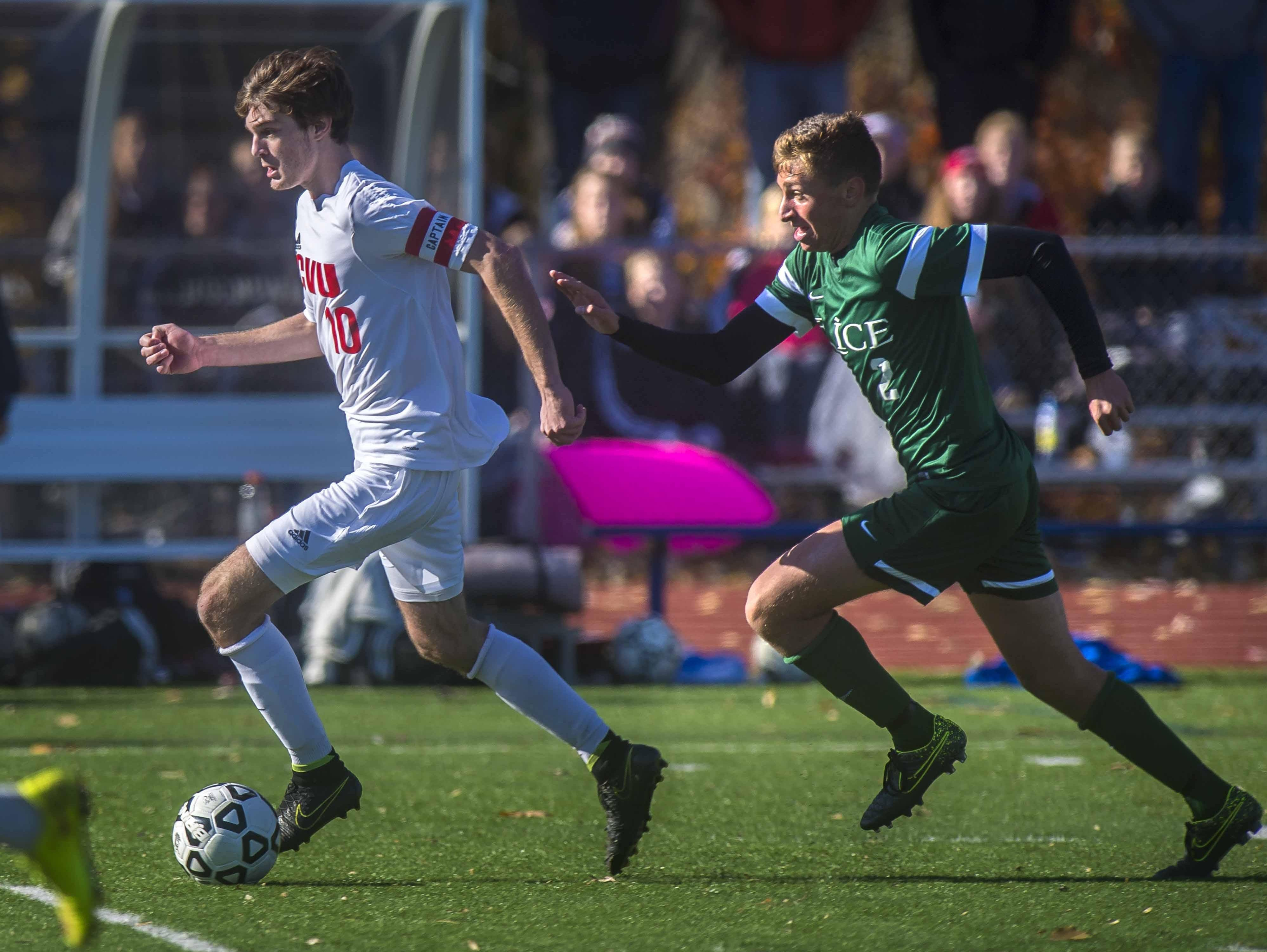 CVU's Cooper O'Connell, left, is chased by Rice Memorial's Brent McKeown in the Division I boys soccer championship in Burlington on Saturday, October 31, 2015.