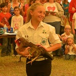 Alexis Hamant showing off her Light Brown Leghorn hen to the crowd at the 2014 Brevard County Fair Market Poultry Auction.