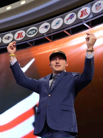 Johnny Manziel gestures on stage after being selected