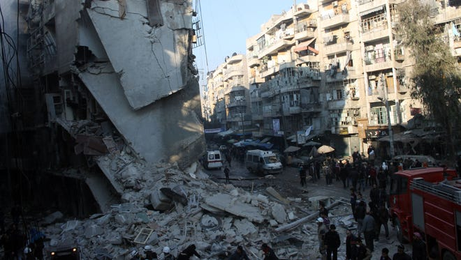 Syrians search for survivors amid the rubble following an airstrike in the Shaar neighborhood of Aleppo on Dec. 17, 2013.