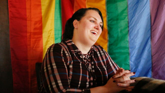 """Destiny Clark, 33, of Odenville, Ala., sits in front of a pride flag for a portrait, Tuesday, Feb. 6, 2018, in Odenville, Ala. The American Civil Liberties Union is suing Alabama on behalf of three transgender individuals, Clark, who is one of them, says that she had gender surgery and sent a letter from her doctor, but the state did not allow her to change her license because an official said the """"treatment was inadequate."""""""