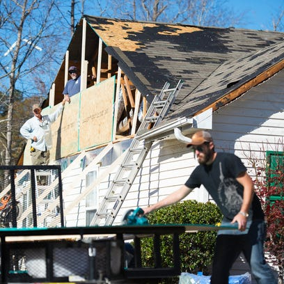 Workers board up a house that lost its roof in Simpsonville
