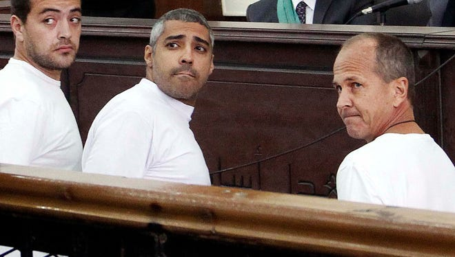 FILE - In this Monday, March 31, 2014 file photo, Al-Jazeera English producer Baher Mohamed, left, Canadian-Egyptian acting Cairo bureau chief Mohammed Fahmy, center, and correspondent Peter Greste, right, appear in court along with several other defendants during their trial on terror charges, in Cairo, Egypt. An appeals court in Egypt on Thursday, Jan. 1, 2015 has ordered a retrial in the case of the three imprisoned Al-Jazeera English journalists. (AP Photo/Heba Elkholy, El Shorouk, File) EGYPT OUT