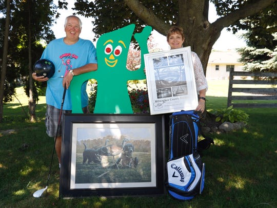 "FILE - Rob ""Gumby"" and Denise Roseff pose with a wooden Gumby board and the prizes for the sixth annual Gumby's Club fundraiser in their backyard in June 2016."