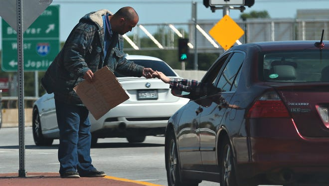 A motorist gives a panhandler money on North Kansas Expressway on Tuesday, May 12, 2015.