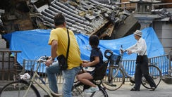 People pause to look at a collapsed house following