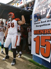 Then-Bengals lineman Jonathan Fanene points upward near a poster dedicated to the Bengals' Chris Henry in December of 2009.
