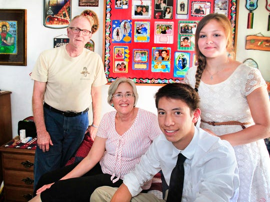 Over the years, Jon and Vickie Nelson, left, who live on West Banta Road on Indianapolis' Far Southside, have hosted more than 30 exchange students, including Giulio Martinelli, 18, from Italy, and Mariya Tokareva, 17, from Russia, who live with them now and attend Perry Meridian High School. They are shown on May 8, 2014 in the bedroom used by Giulio, where a mural of photos of former exchange students hangs on the wall.