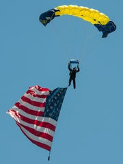 Brad Woodard of the United States Navy Seals Leap Frogs parachutes onto the beach during the National Anthem at the OC Air Show. The show includes acrobatics and formations by civilian and military aircraft, including the U.S. Air Force Thunderbirds. The OC Air Show continues Sunday, with show center at 16th Street oceanside.