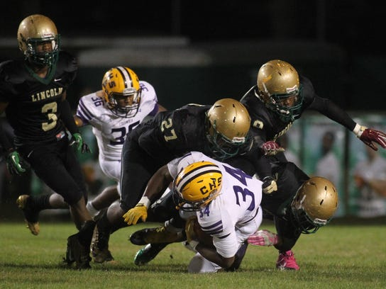 Columbia's Kamario Bell is tackled by Lincoln's Lorenzo