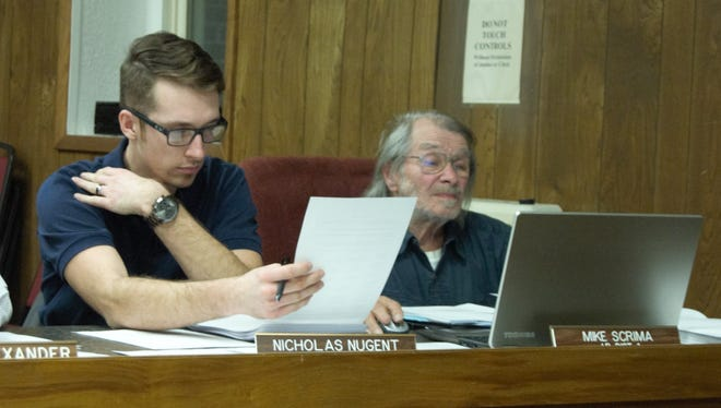 Marion County justices of the peace (from left) Nicholas Nugent and Mike Scrima look over a proposed ordinance Tuesday night at the Marion County Quorum Court meeting. Justices tabled a proposed ordinance that would have consolidated the county's 16 polling places into a half-dozen voting centers.