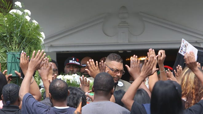 Friends and family surround the casket of 20-year-old Terrance Kellom as it is brought out following funeral service at Trinity Chapel Funeral Home, putting their hands up to block the news media from taking photographs from the front of the funeral home's sidewalk on Wednesday.