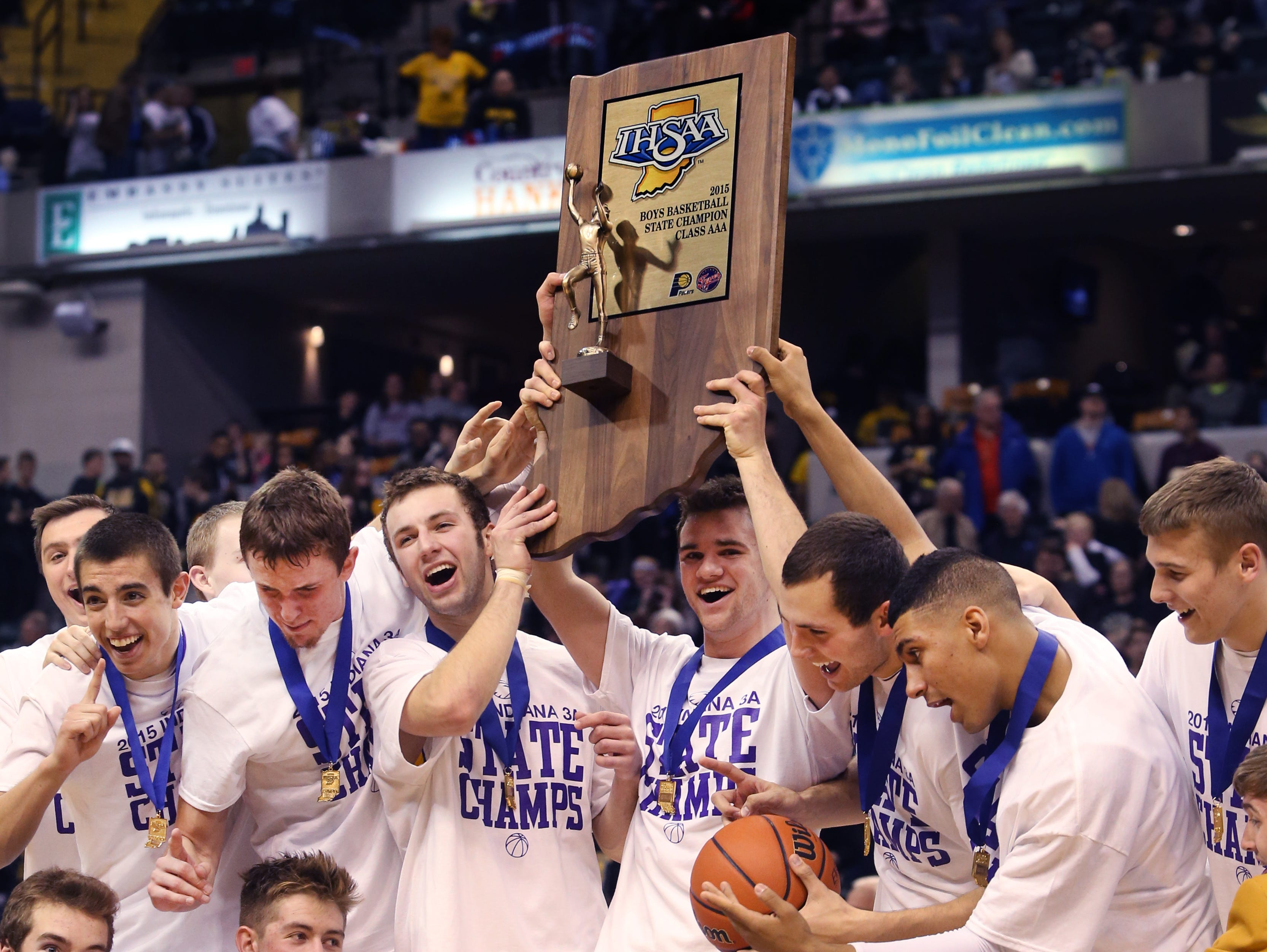 Guerin Catholic players celebrate after defeating Griffith 62-56 in the state finals to win the IHSAA Class 3A Boys State Basketball Championship at Bankers Life Fieldhouse March 28, 2015.