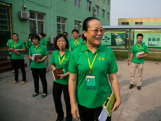 CEO Yuqi Zhao, center, gives a tour of the Heibei Qimei Science and Technology Co., Ltd,   Handan China Tuesday Sept. 9, 2014.