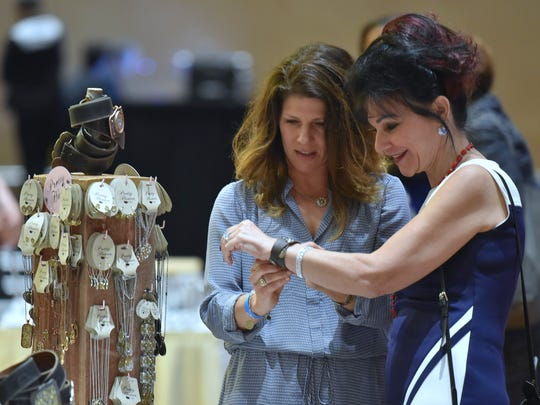 Ingham Co. 30th Circuit Court Judge Rosemarie Aquilina, right, is assisted by Pretty Hunter founder Tricia Kay Auten, left, 45, of Commerce Twp., as she tries on Auten's hand-crafted ammo jewelry before the awards ceremony.