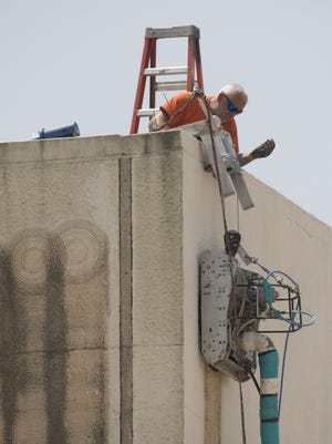 Contractors working on the old Pensacola News Journal building at the corner of Jefferson and Romana Streets are using a robot to remove asbestos from the stucco facade.