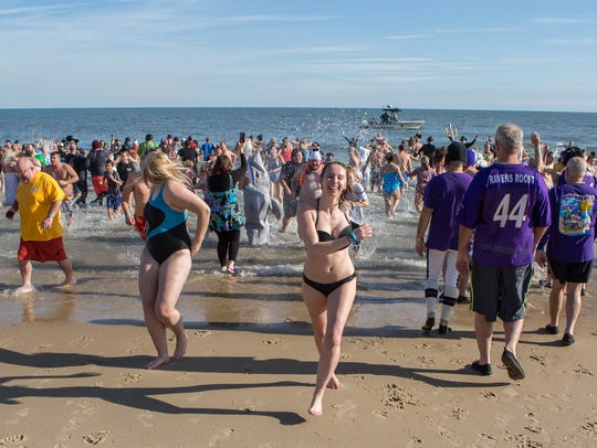 Crowds of beachgoers run away from the ocean during