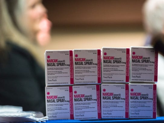 A stack of Narcan nasal spray sits on a table at an