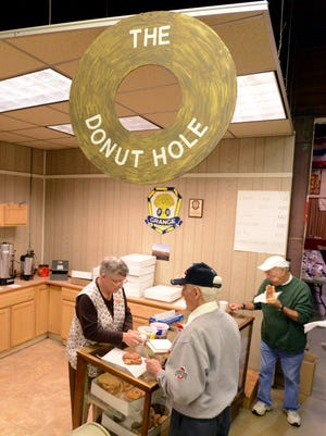 Penny Dennis serves doughnuts to customers at The Donut Hole stand in the Art Hall at the Fairfield County Fair. Dennis said the stand, run by the Fairfield County Pomono Grange, sells about 200 dozen doughnuts during the fair.