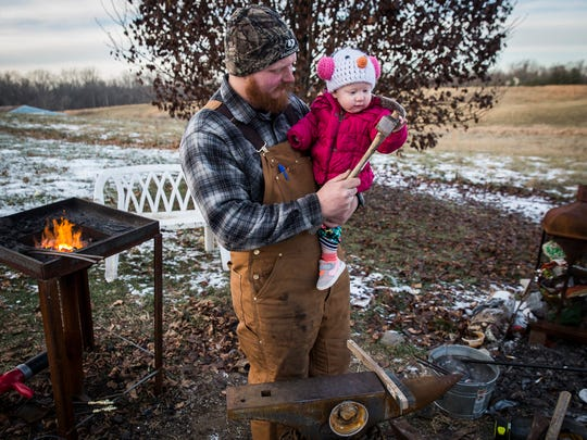 Blacksmith Seth Gibson takes a break from working on a belt buckle to spend time with his daughter, Willow.