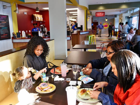 York City property maintenance inspector Cliffonda Stokes, second from right, eats dinner with her granddaughter Serenity Wright, 2, far left; daughter Strangé Henderson, second from left; and daughter Shania Henderson, far right, during a soft open at Isaac's on the Fly Thursday, March 23, 2017, in York. The restaurant is the Lancaster-based sandwich chain's first in York City, and is also the first to feature a fast casual concept and a breakfast menu. The restaurant officially opens March 27.