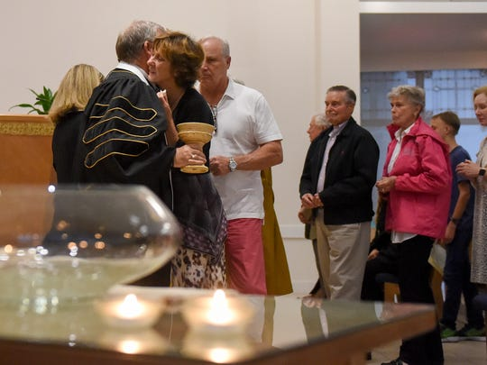 Linda Proctor hugs Dr. Robert T. Baggott as her husband Donnie Proctor waits to the right during a memorial at Community Church of Vero Beach for those who died in the mass shooting at Las Vegas's Route 91 Harvest Festival music concert on Sunday, Oct. 1.