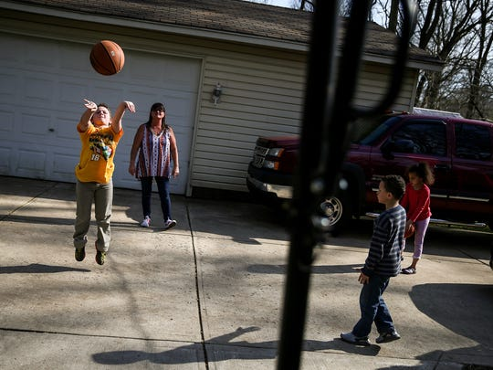 Bryce, 9, his grandmother Tammy Hackman, and cousins Markell and Mya (at right) shoot hoops at Hackman's Indianapolis home, Thursday, April 12, 2018. When Bryce's mother Tristan Hackman died of a drug overdose in 2015, several of her organs were donated. Knowing her donation saved others' lives has helped her family heal.