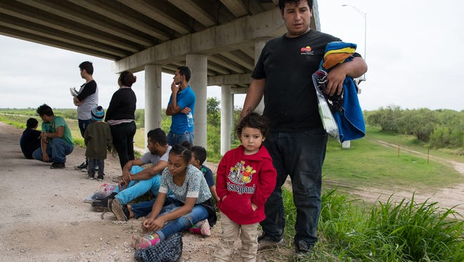 Lester Morales, 27, from Guatemala and his 3-year-old son, José Fernando wait to be transported to a processing center by U.S. Border Patrol after being found near McAllen, Texas on  June 19, 2018.