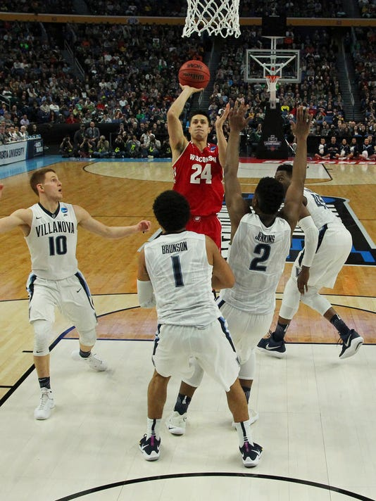 Wisconsin guard Bronson Koenig (24) takes a jump shot while defended by Villanova guard Donte DiVincenzo (10), guard Jalen Brunson (1) and forward Kris Jenkins (2) during the second half of a second-round men's college basketball game in the NCAA Tournament, Saturday, March 18, 2017, in Buffalo, N.Y. (AP Photo/Bill Wippert)