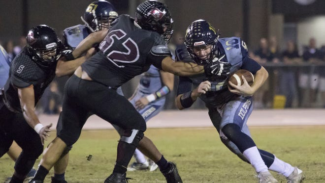 Quaterback Tyler Phelps (10) carries the ball during the Gulf Breeze vs. Navarre football at Navarre High School Oct. 28.
