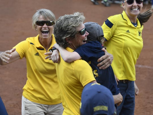 Michigan coach Carol Hutchins hugs Wolverines softball superfan Natalie Harper, 12, after the victory.
