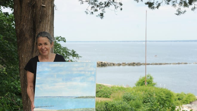 Mimi Schlichter holds one of 25 paintings she created working in a borrowed home overlooking Megansett Harbor, near the North Falmouth spot where she vacationed as a child.    Merrily Cassidy/Cape Cod Times