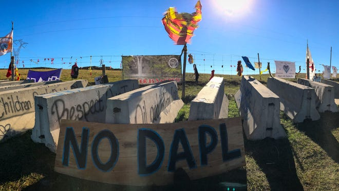 Protest signs line the fences of the land where the Dakota Access pipeline is to be constructed north of the Oceti Sakowin Camp Thursday, Sept. 29, 2016, near Cannon Ball, N.D.