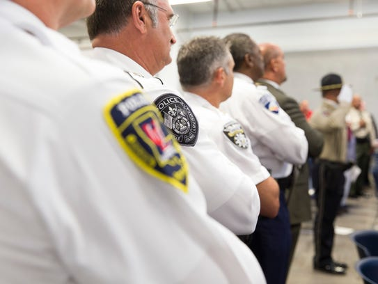 Local police chiefs cover their hearts during national