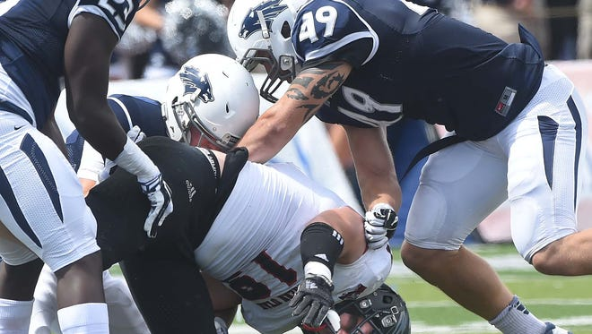 Nevada's Brandon Thompson, left, Duran Workman and Austin Fletcher team up to force a fumble from Southern Utah's Chandler Allphin during the Pack's win Saturday