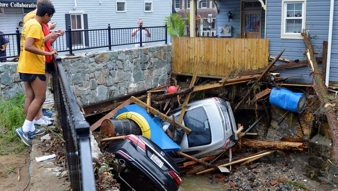 Residents gather by a bridge to look at cars left crumpled in one of the tributaries of the Patapsco River that burst its banks as it channeled through historic Main Street in Ellicott City, Md., Monday, May 28, 2018.