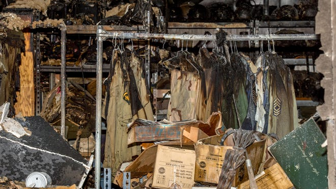 The charred remains of military uniforms still hang on a rack in Jerry Lance's burned out garage Wednesday, Oct. 14, 2020 in Hanna City. A longtime collector of military memorabilia, the Navy veteran lost tens of thousands of dollars' worth of vintage uniforms, helmets, equipment and other collectibles when a fire tore through the building.