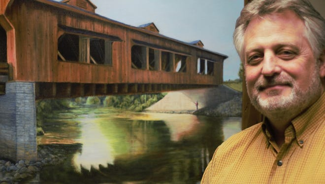 Marion County Engineer Brad Irons stands next to a print of a painting of King's Mill wooden covered bridge, which hangs outside of his office. The print was donated by artist Richard Woy, a former Marion resident.