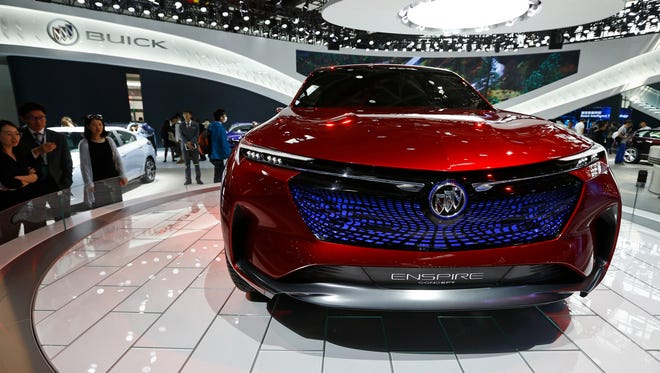 In this April 26, 2018, file photo, visitors look at a Buick Enspire concept car on display at the China Auto China in Beijing. China has announced it will reduce auto import duties effective July 1 following promises to buy more U.S. goods and end restrictions on foreign ownership in the industry. The Finance Ministry said Tuesday, May 22, 2018,  that charges for many imported vehicles will be reduced from 25 percent to 15 percent.