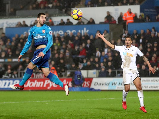 Arsenal's Henrikh Mkhitaryan, left, heads the ball on goal during the English Premier League soccer match between Swansea City and Arsenal at the Liberty Stadium, Swansea, Wales, Tuesday, Jan. 30, 2018. (Nick Potts/PA via AP)