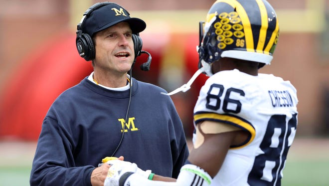 Michigan Wolverines head coach Jim Harbaugh congratulates wide receiver Jehu Chesson following his touchdown against the Maryland Terrapins at Byrd Stadium.