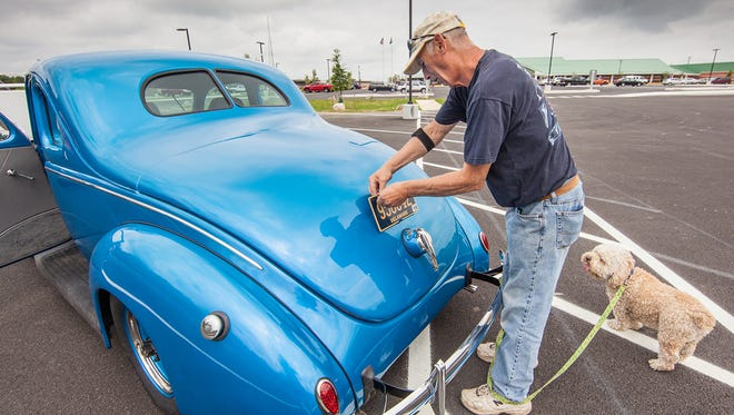Nick Liberman gets some help from his dog SABA to attach a new license plate on his 1939 Ford that he just finished restoring.