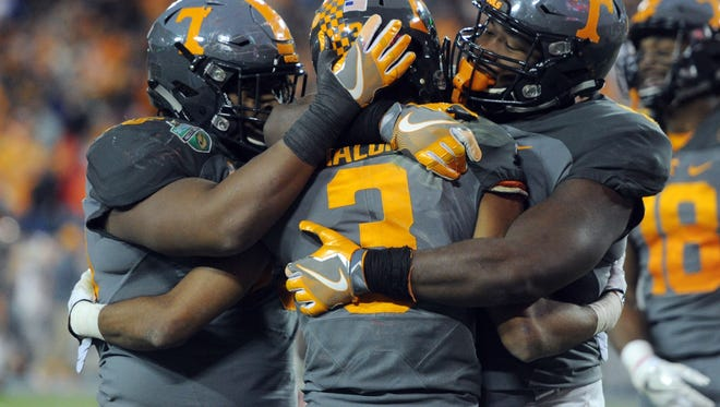 Tennessee offensive lineman Jashon Robertson (75), left, and Tennessee offensive lineman Drew Richmond congratulate Tennessee wide receiver Josh Malone (3) after Malone scored a touchdown against Nebraska in the Franklin American Mortgage Music City Bowl at Nissan Stadium in Nashville, Tenn., Friday, Dec. 30, 2016.