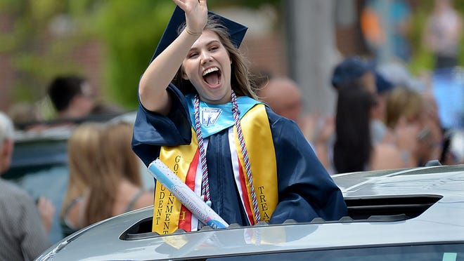 Franklin High School graduate Gina Schratz waves from her sunroof during the school's graduation parade on Friday, June 5.