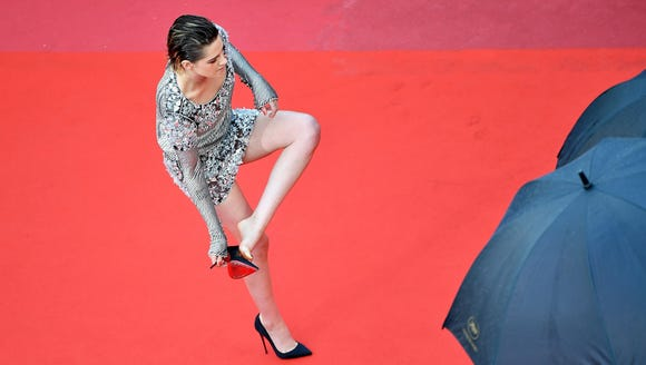 Kristen Stewart removes her shoes on the red carpet