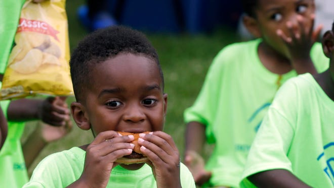 Davion Curlee, 4, of Milwaukee, enjoys a hamburger with other children from the Boys and Girls Clubs as they enjoy a community event at Franklin Square Park.