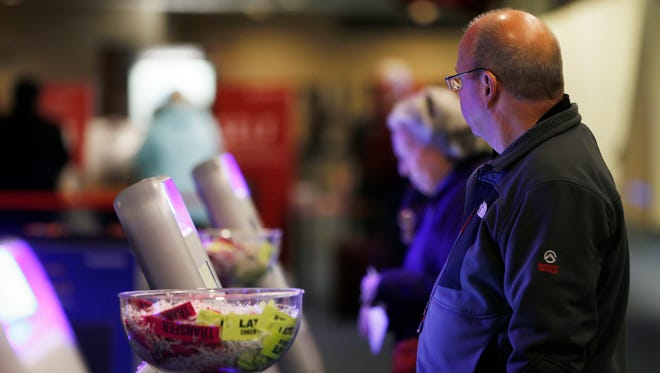 Airport travelers check their baggage at Southwest ticket kiosks at Mitchell International Airport last month.