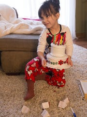 Emily Theisen, 4, carries a toy birthday cake at her home in Noblesville, Friday, January 13, 2017. Theisen must be fed through a port, and the cake is a stand-in, as she isn't able to eat a  baked one.