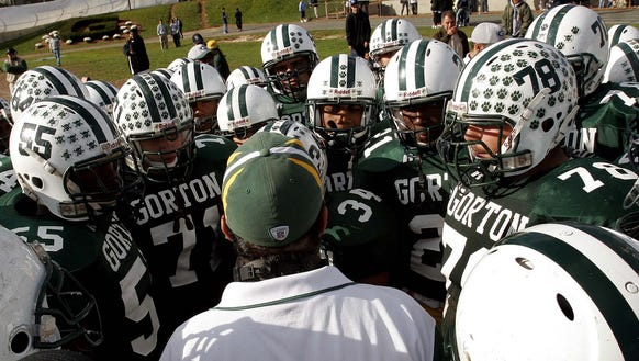The Gorton football team and coach Dan DeMatteo huddle up during a game against New Rochelle at Gorton High School in Yonkers. Gorton is one of eight high schools in Yonkers that will merge into two varsity football teams.